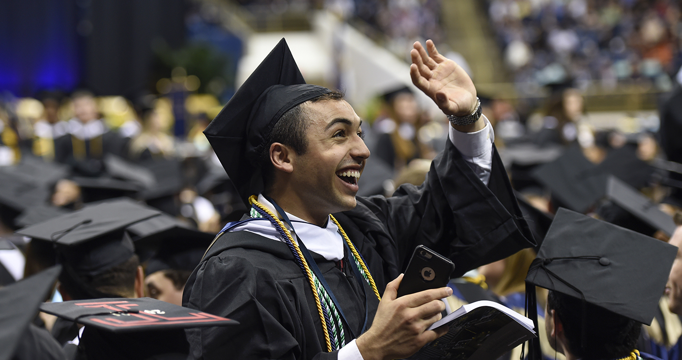 graduate in a cap and gown waving