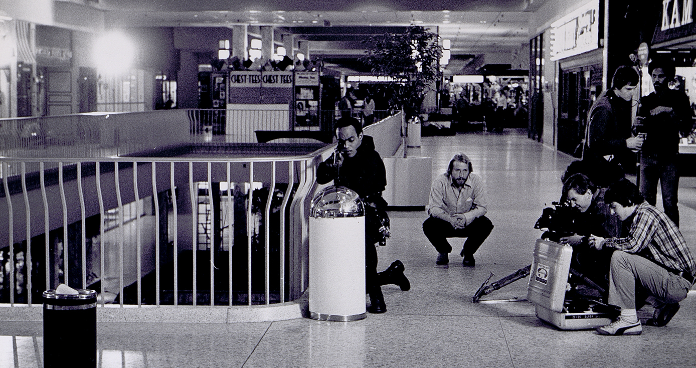 a black and white photo of a camera crew shooting a scene in a mall