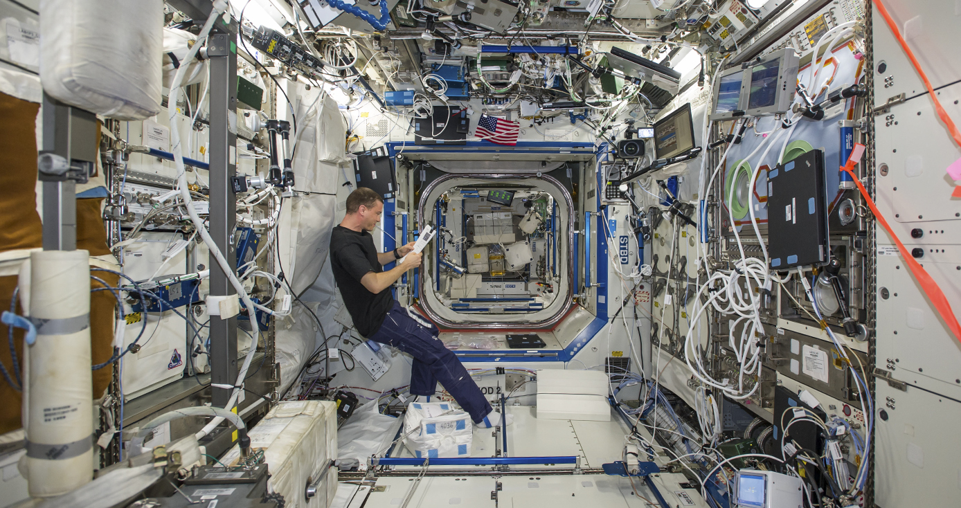 flight engineer Reid Wiseman of NASA aboard the International Space Station, reading a sheet of paper amidst the inside of the station.