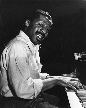 Black and white historical photo of jazz musician Erroll Garner playing the piano.