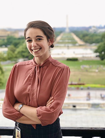 A woman in a red top standing in front of a city scape