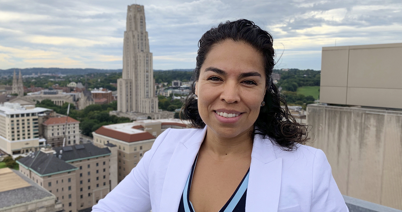 Gelsy Torres-Oviedo in white jacket over blue shirt, standing on a rooftop overlooking Pitt campus with Cathedral of Learning prominently in the background