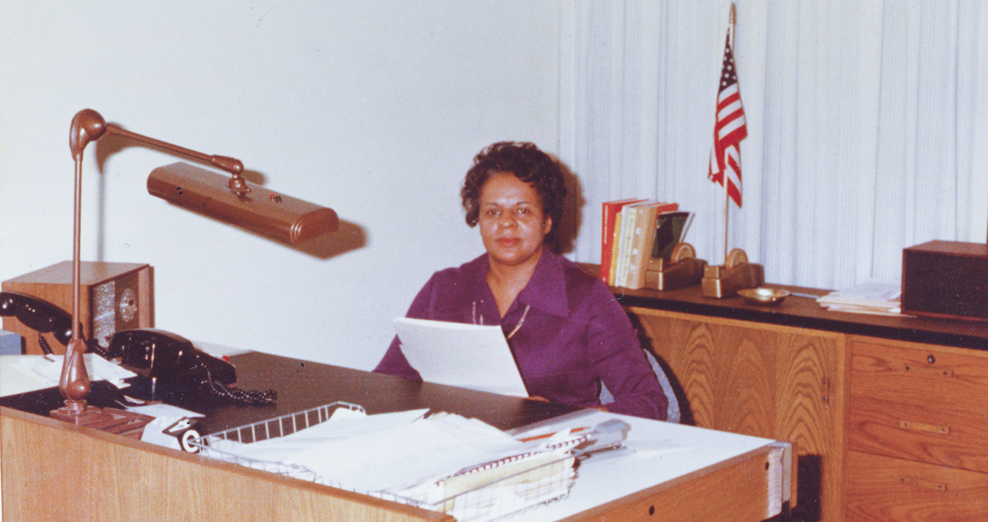 Gertrude Wade in a purple dress shirt sitting at a desk.
