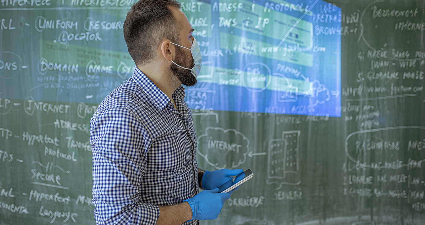 a teacher in a mask and gloves holding a tablet in front of a chalkboard