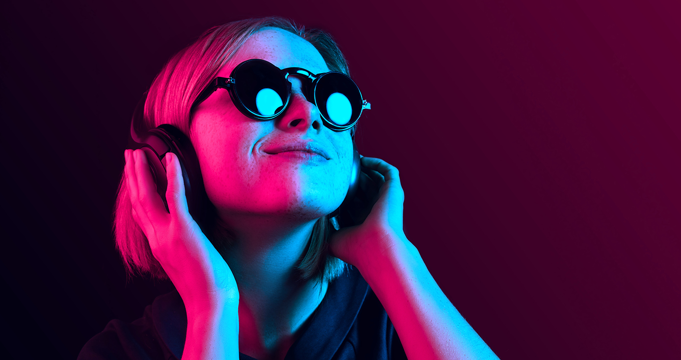 A person in sunglasses listening to music on headphones in a neon pink-blue light