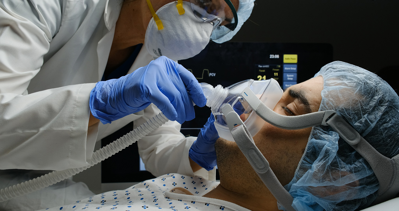 A physician adjusts a mask on a patient lying down