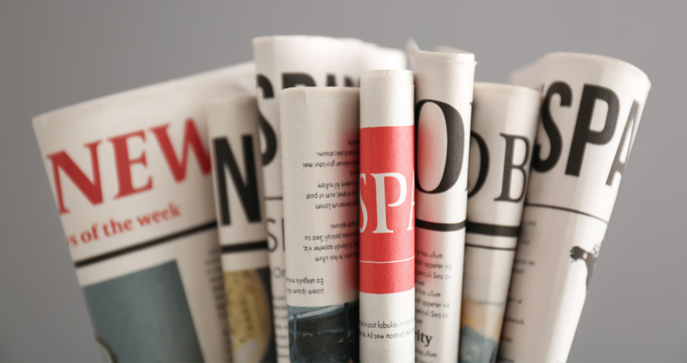 several folded newspapers on a gray background