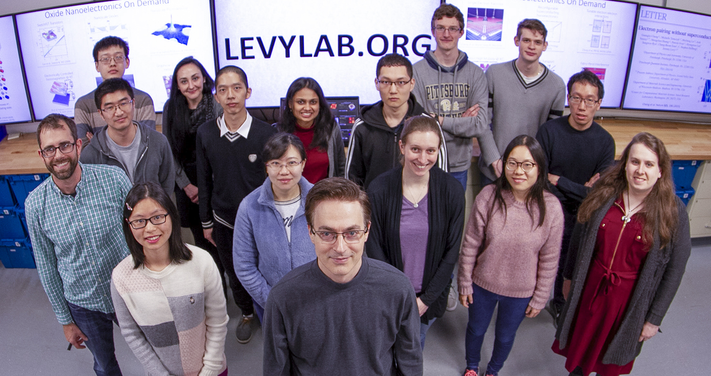 Jeremy Levy, a Distinguished Professor of Condensed Matter Physics in the Department of Physics and Astronomy, stands in front of his team in Levy Lab.