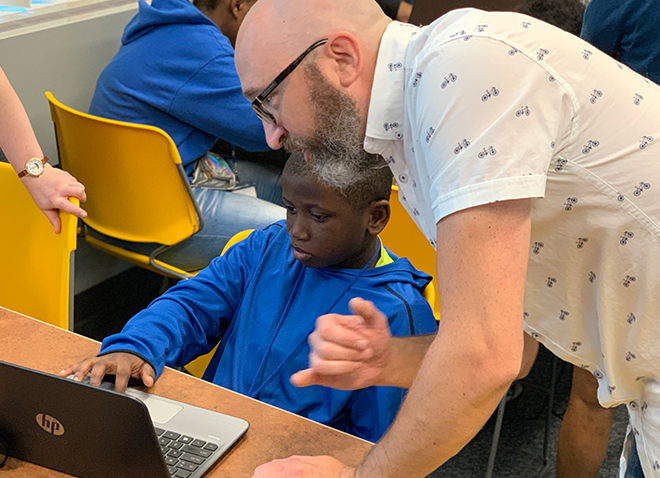 an instructor leaning near a young student using a laptop
