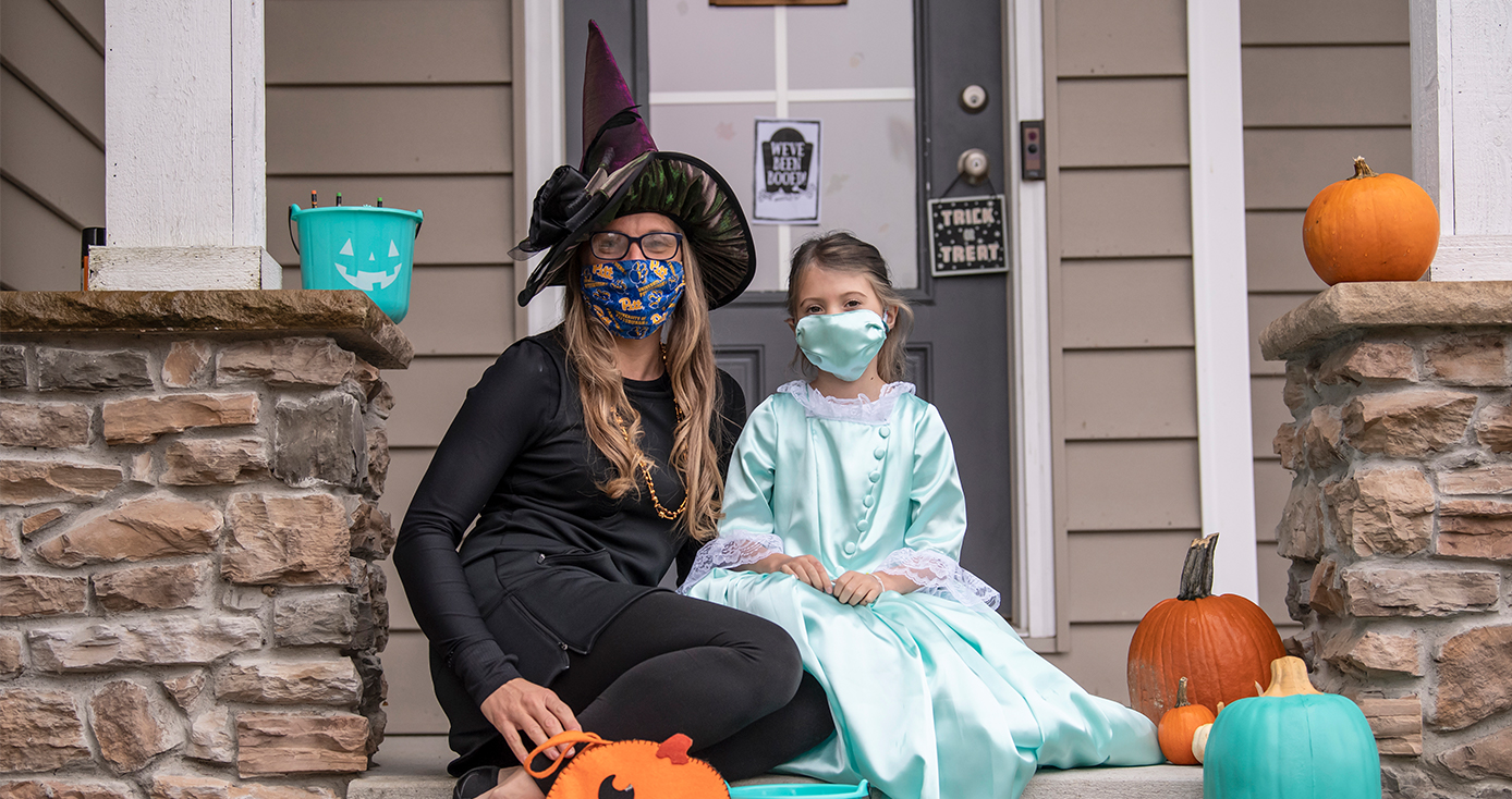 A woman and her child in costume, sitting in face masks on a porch