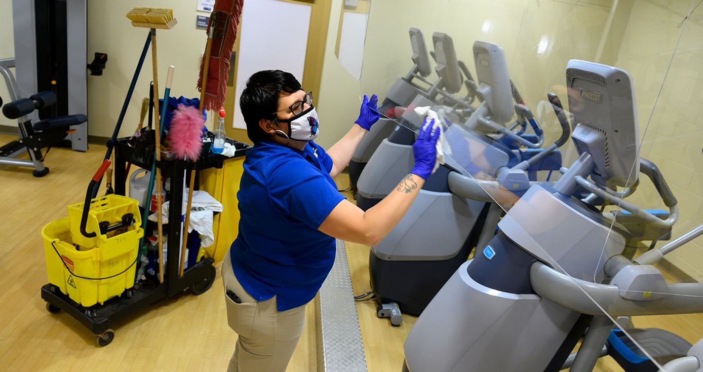 A person in blue Pitt protective gear cleans exercise equipment