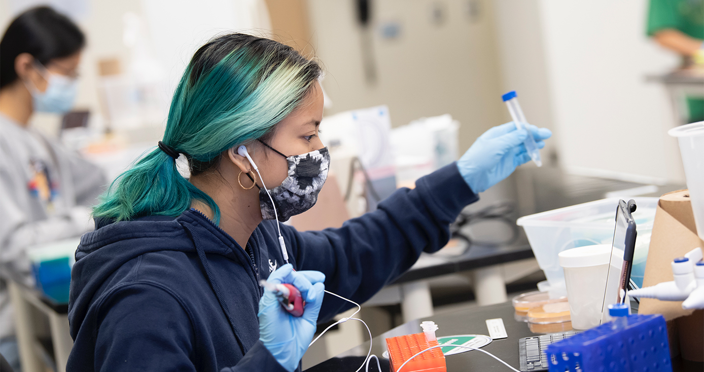 A student with blue-green and black hair uses lab equipment