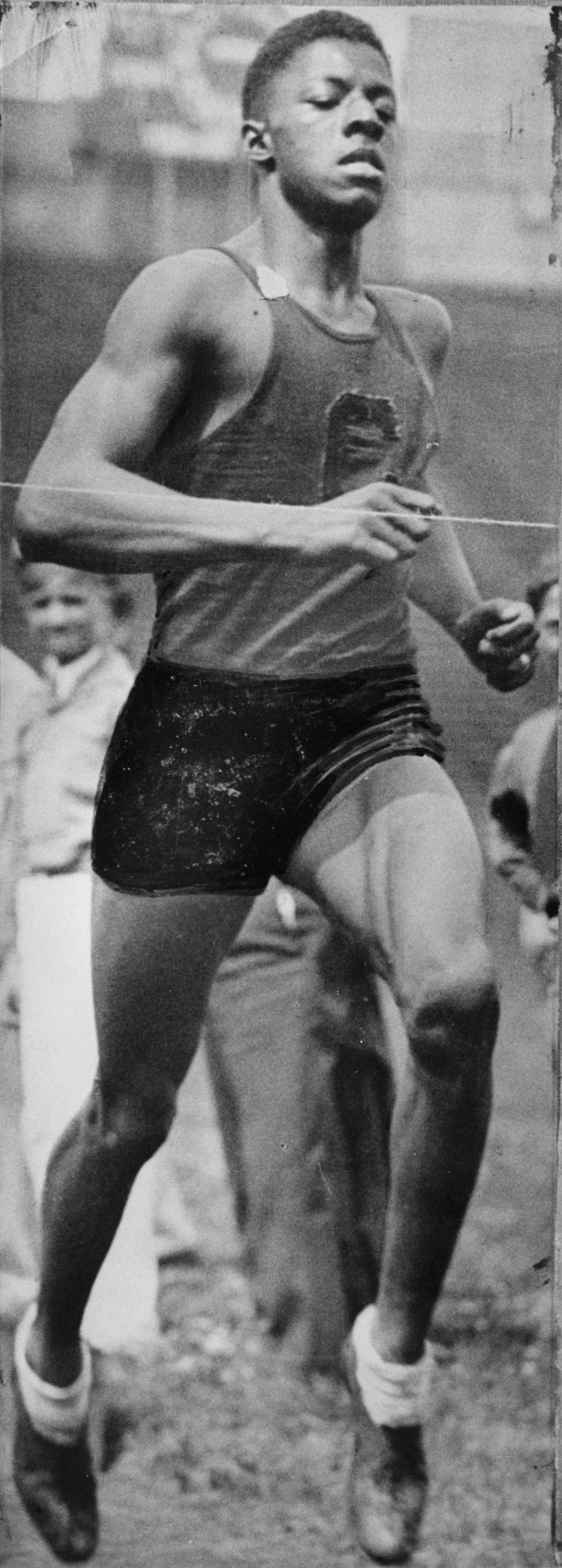 Black and white historical newspaper photo of John Woodruff running in the 800-meter race in the 1936 Olympics in Berlin, Germany