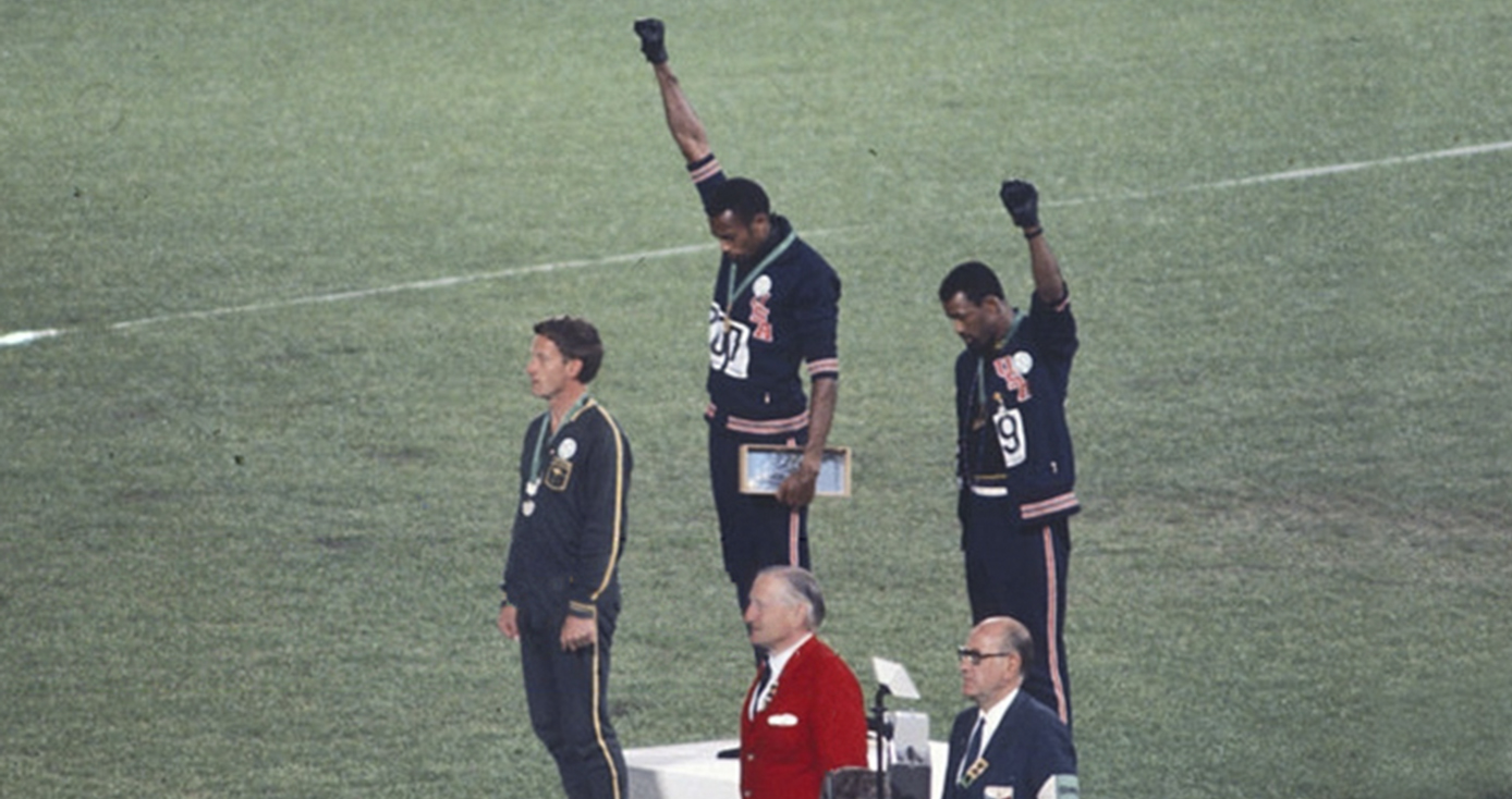 Tommy Smith and John Carlos on a podium holding their fists in the air