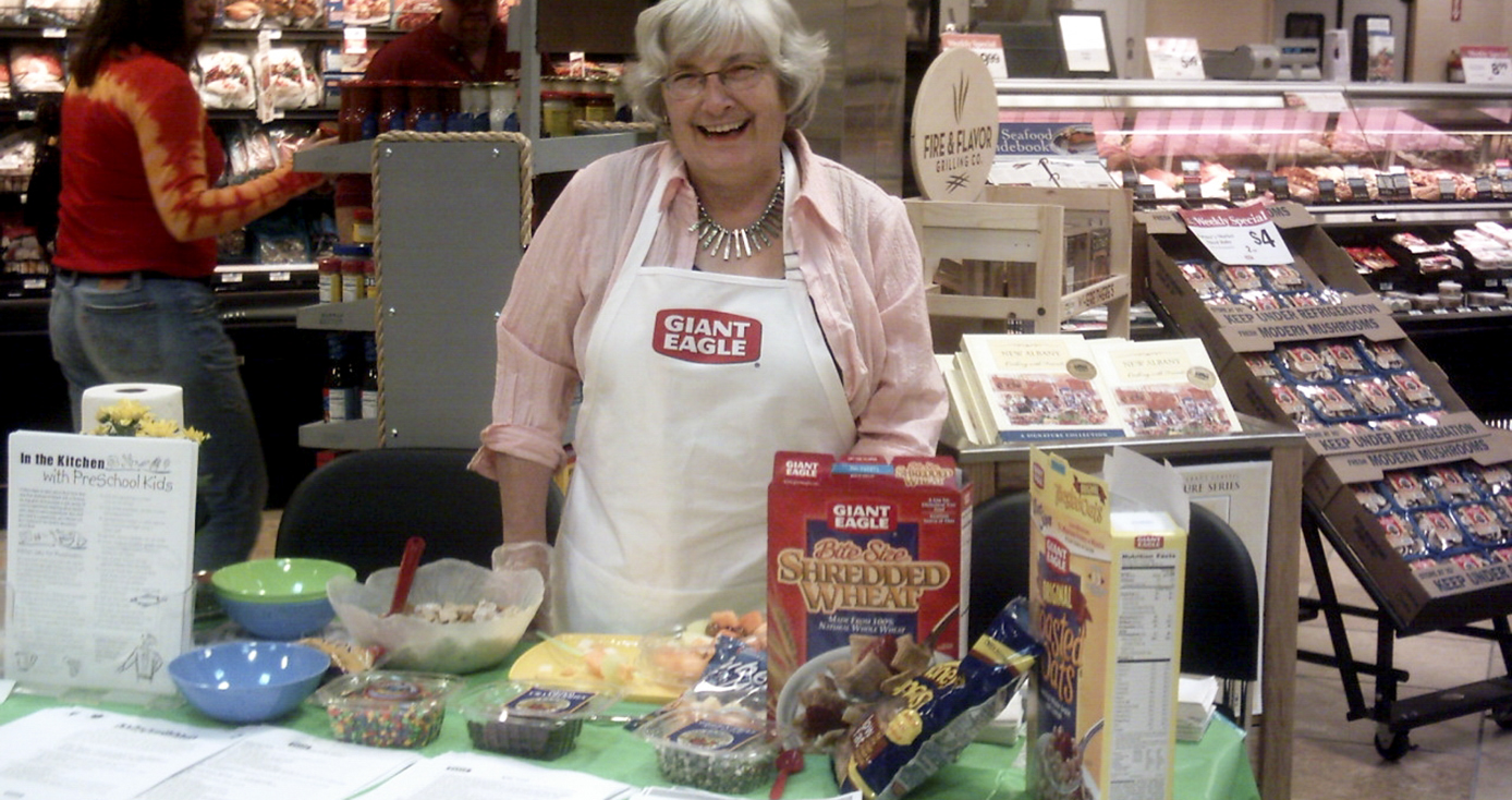 a woman in a Giant Eagle white apron standing behind a table displaying various cereals