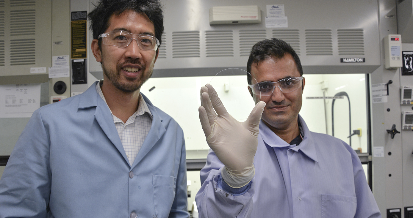 two men in lab coats, one holding a circle of glass