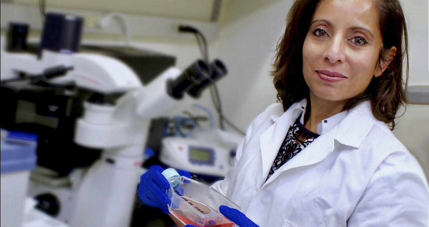 Maliha Zahid in white lab coat and wearing blue gloves holding a clear bottle of liquid in a lab setting