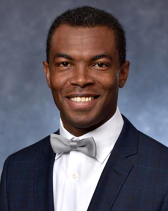 A man in a black suit, white shirt and silver bow tie