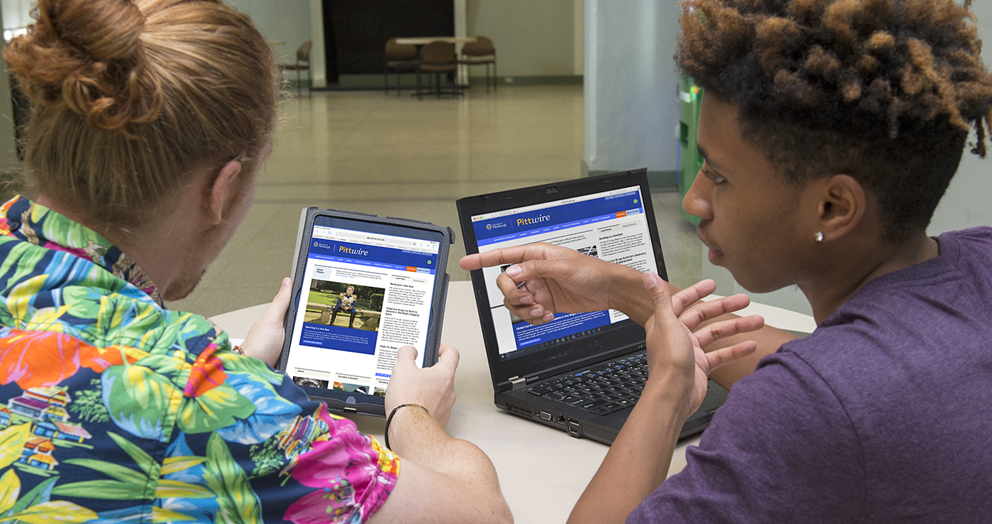 Two male students reading PIttwire online, one on a tablet and the other on a laptop computer.