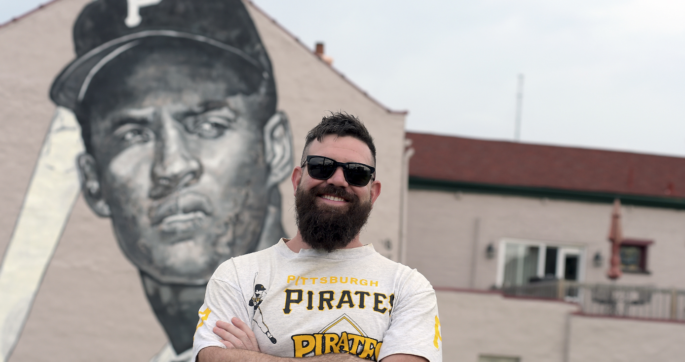 Pitt alumnus Jeremy M. Raymer in a PIttsburgh Pirates shirt standing in front of a mural he painted of Pirates baseball player Roberto Clemente