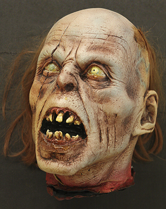 a zombie head with reddish hair, big blue veins and grotesque yellow teeth