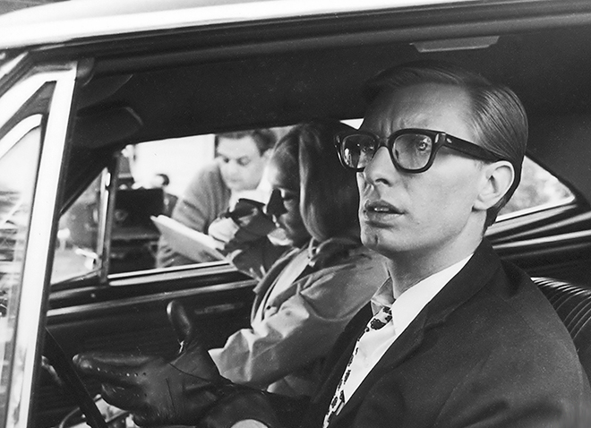 Black and white still image from Night of the Living Dead showing man and woman in front seat of car