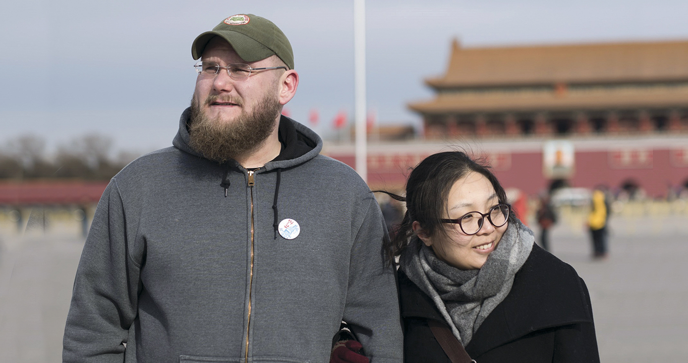 Carl Setzer and Liu Fang outside, wearing cool-weather clothing, in front of a scene in China