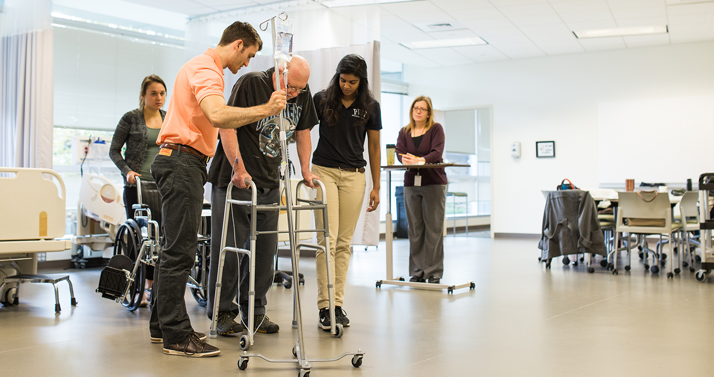 Therapists assist a person in a walker.