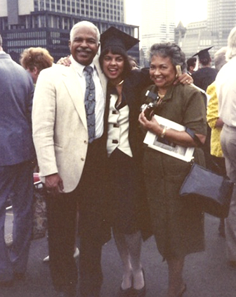 a woman in graduation garb with her arms over her parents' shoulders: dad in a white suit, mom in a green dress
