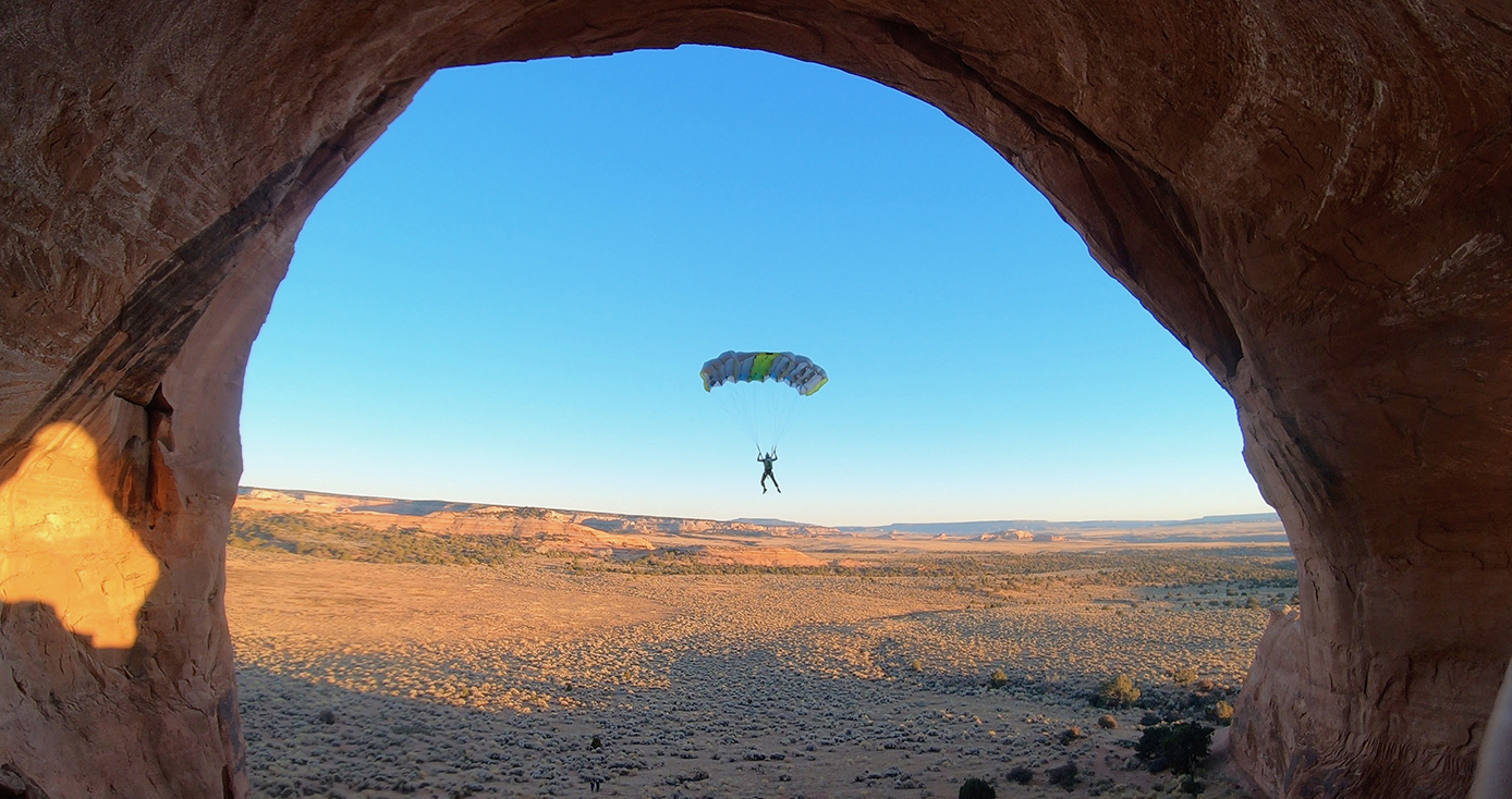 A man BASE jumping through a natural rock arch
