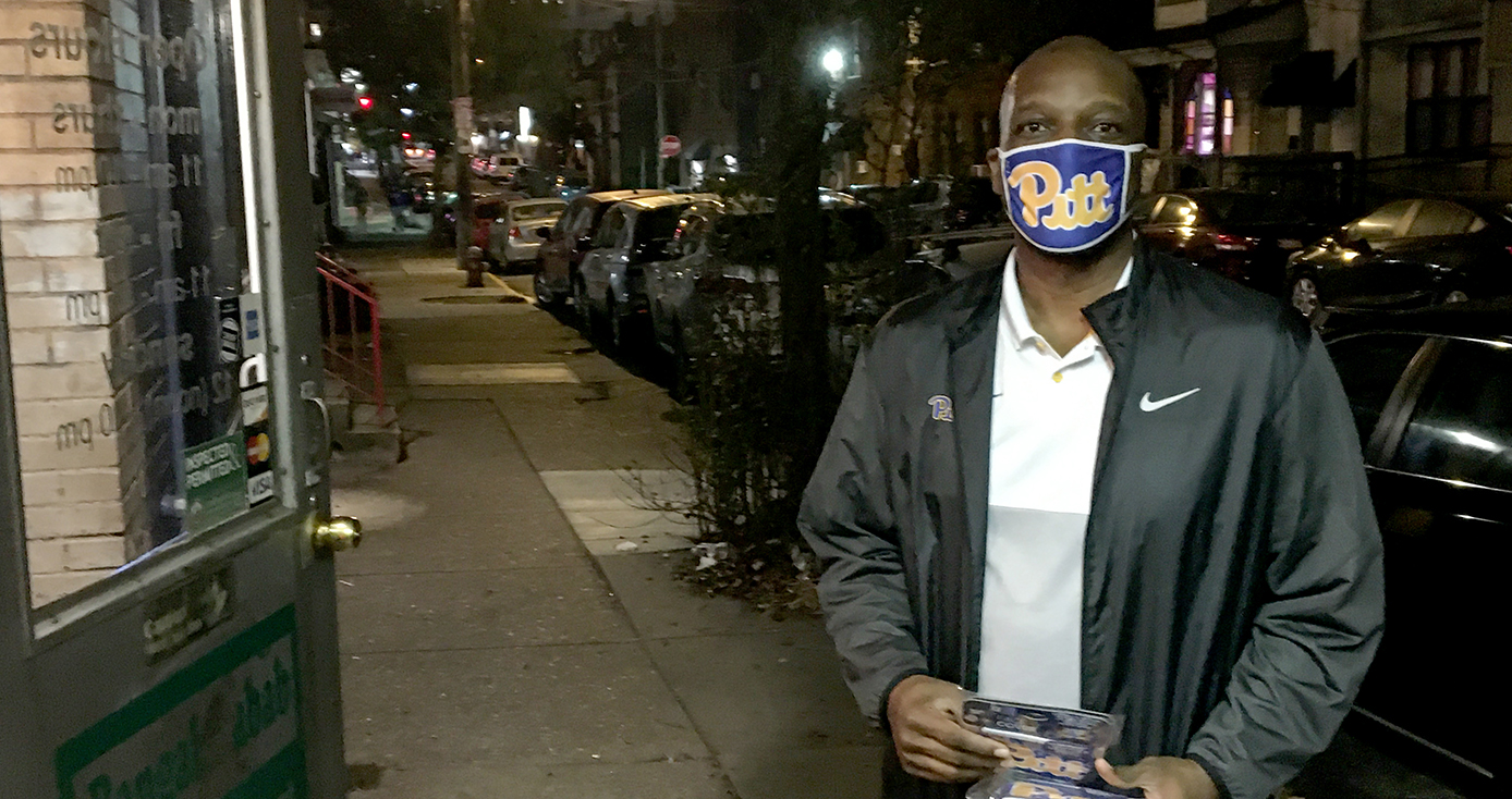A man in a Pitt face mask and black jacket on a city street