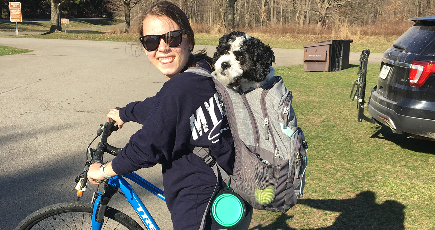 Katie Kniess with sunglasses on bicycle with Oliver, a black and white dog, in her backpack