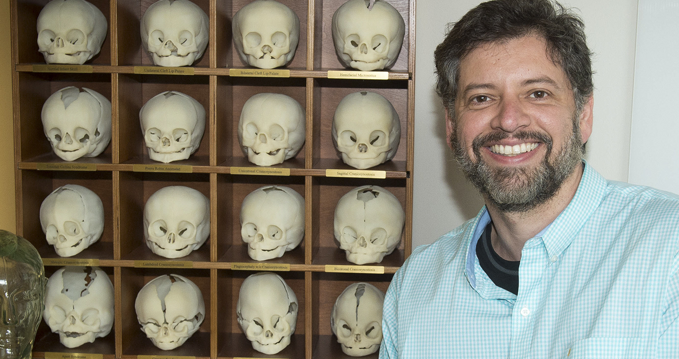 bearded man in front of a shelf of replica skulls