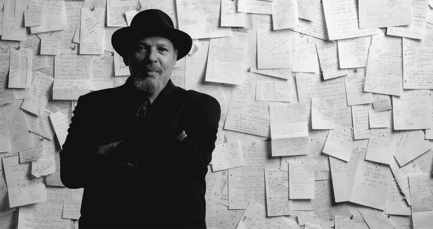 A man in a black coat and hat in front of a wall covered in paper