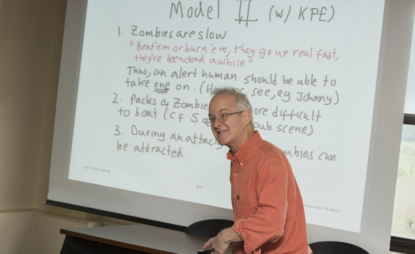Ermentrout in an orange shirt in front of a screen with some rules of the math lesson on it