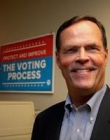 Headshot of David Thornburgh with poster saying: Protect and Improve the Voting Process