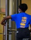 A student in a blue Pitt shirt opens a door