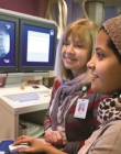 An instructor helping a student with a health information systems program