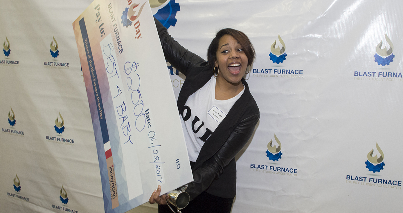 young woman with a big smile holding a novelty-sized check