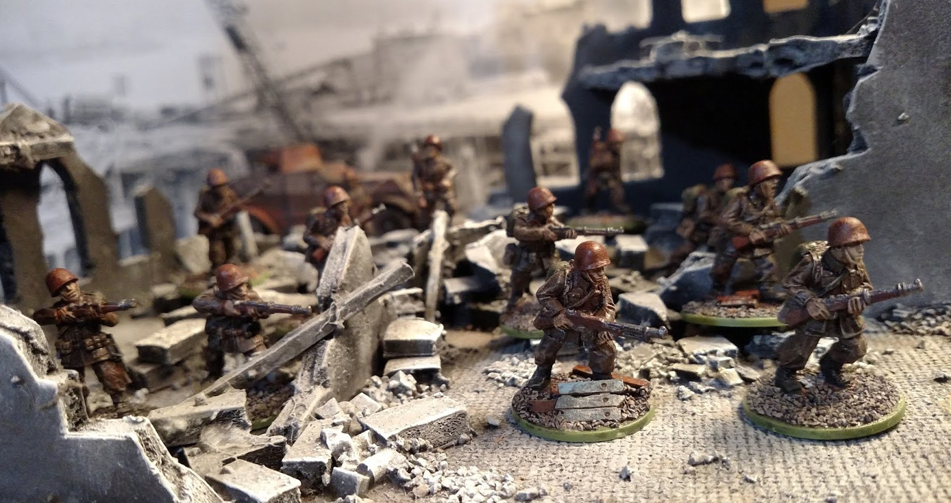 Miniature figures of soldiers in a tabletop scene.