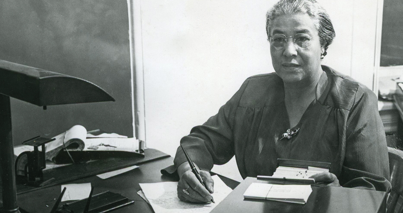 Ella P. Stewart at a desk, writing on a paper, in a black and white photograph.