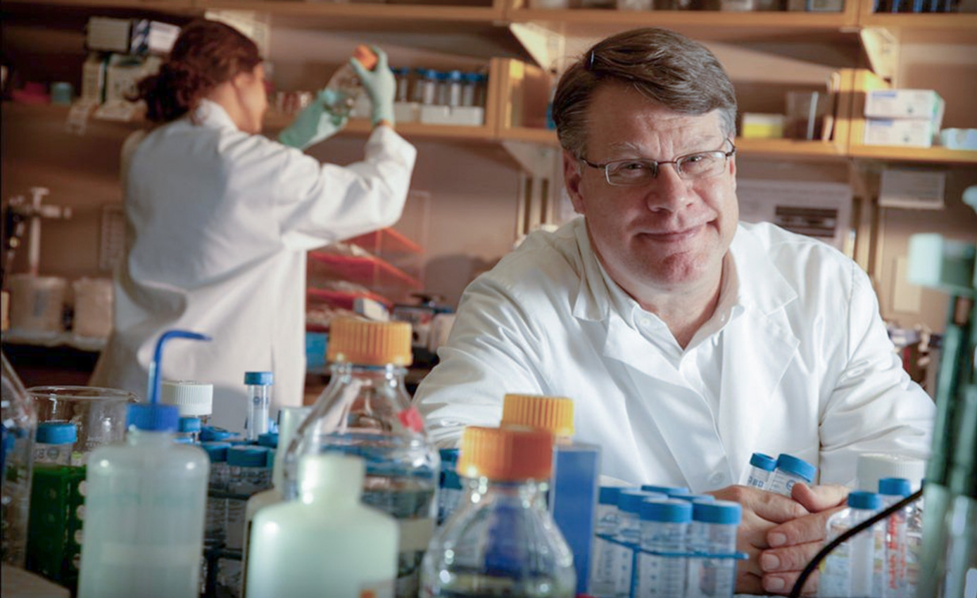 Bennett Van Houten, professor of pharmacology and chemical biology at theUniversity of Pittsburgh School of Medicineand UPMC Hillman Cancer Center, in lab with bottles and vials in the foreground and another lab worker with back to the camera in the background working with items on shelves