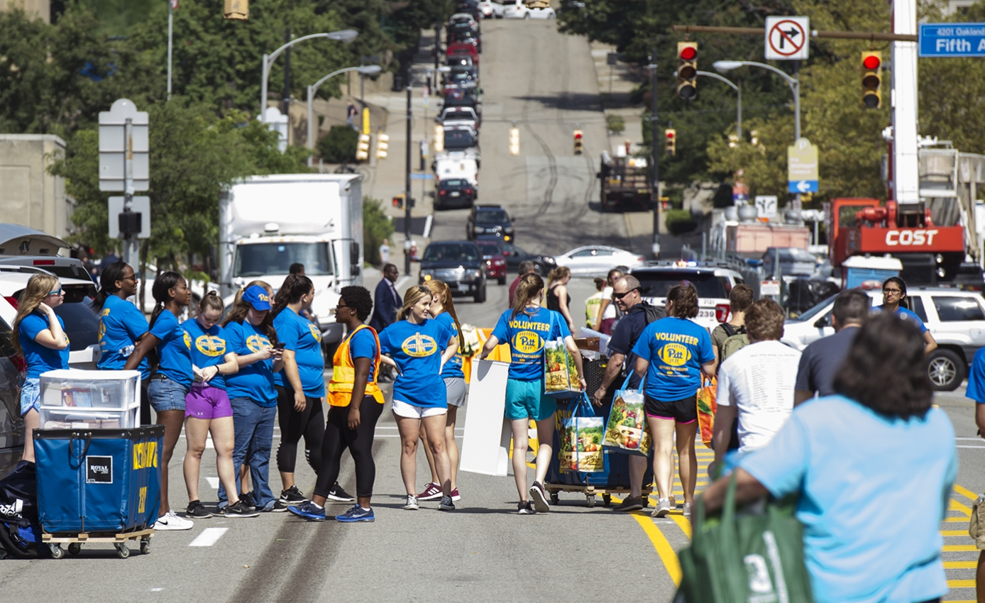 Large group of students gathered on a street closed to traffic,  wearing Pitt blue and gold Arrival Survival volunteer T-shirts during a previous move-in week
