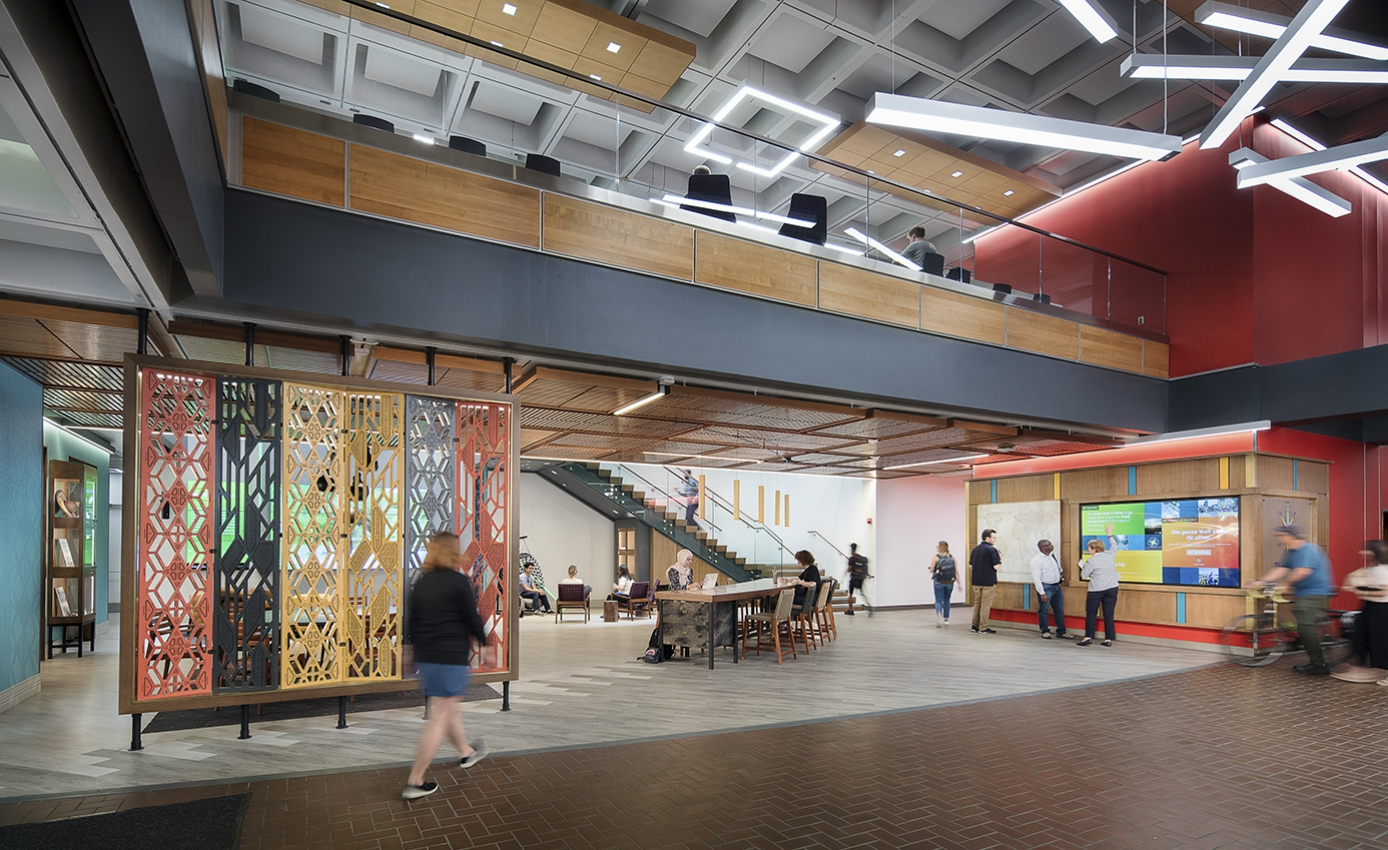Overall view of the first floor of the Pitt Global Hub, showing colorful furnishings and people walking and sitting in the area