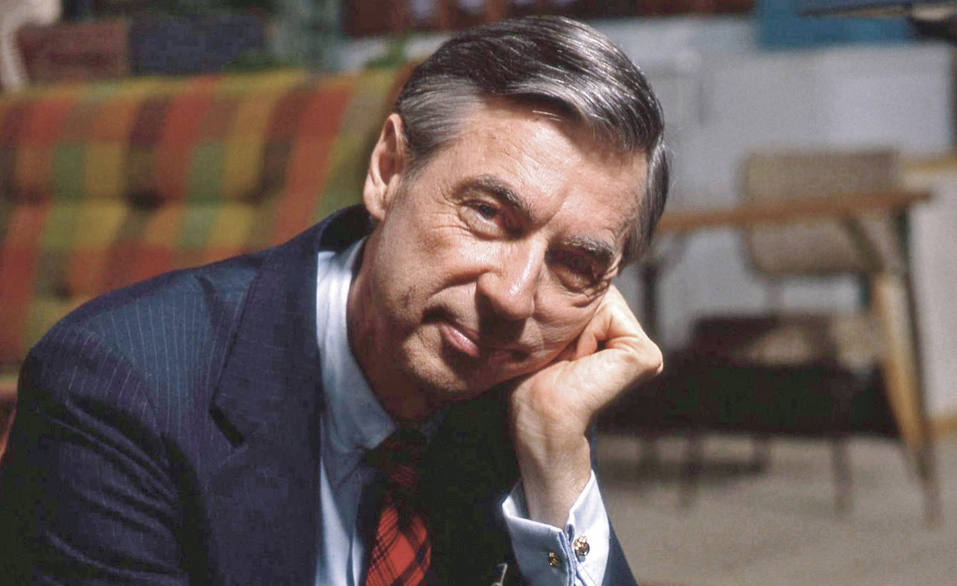 Fred Rogers leaning his head on his hand, looking into camera, in suit jacket and tie, with couch and chair in the background