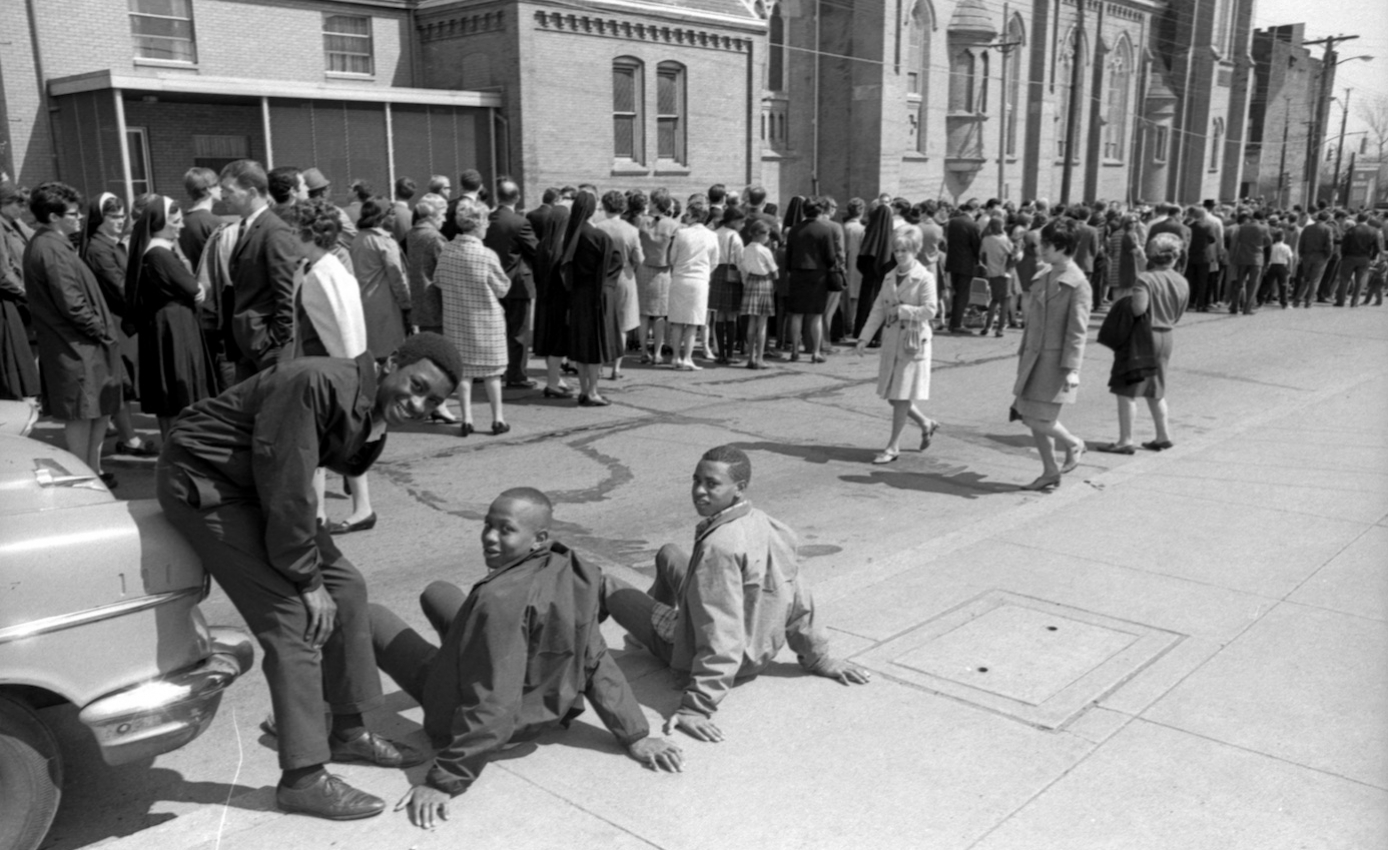 Black and white historical photo of gathering of crowd of people on street and sidewalk in Pittsburgh after Martin Luther King Jr. assassination in 1968. three African-American boys in the foreground.