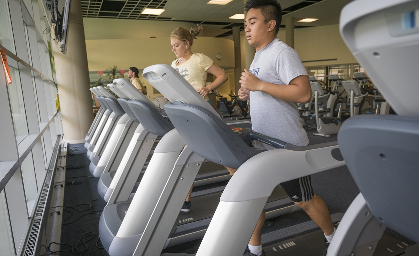 Two students, one female and one male, running on treadmills