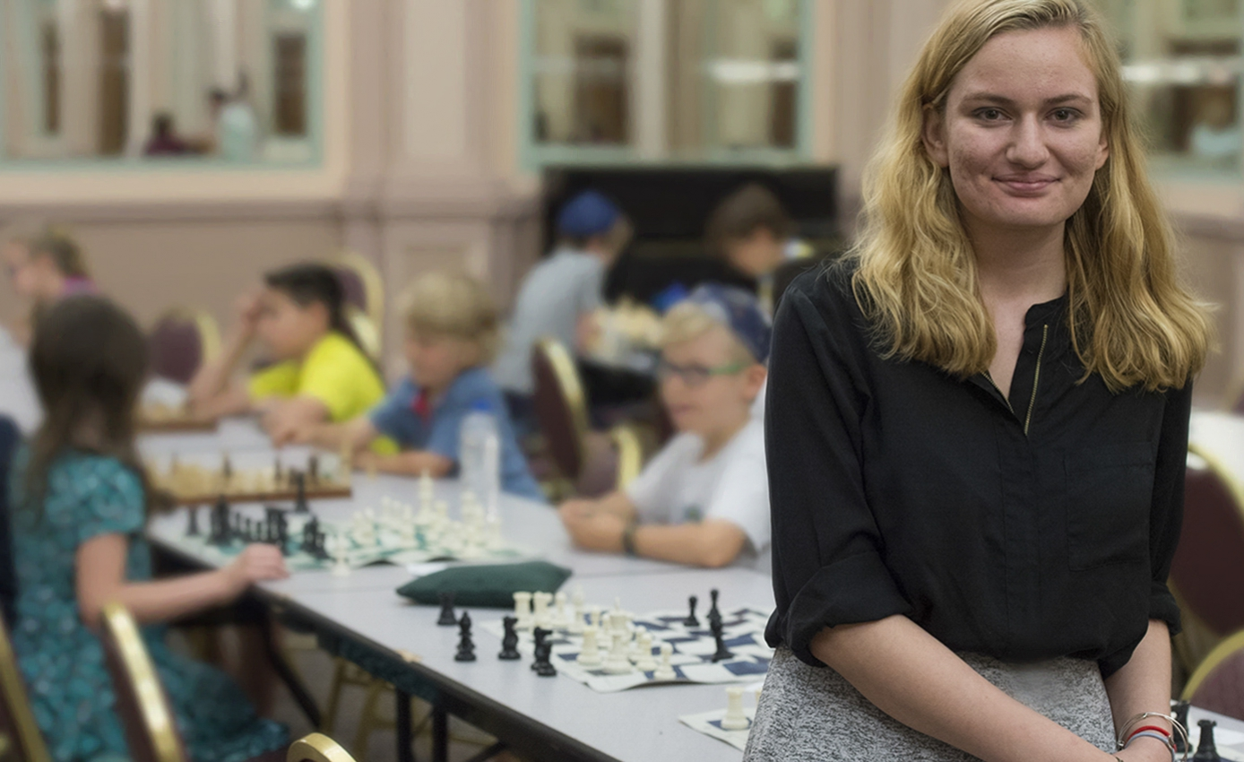 Young woman with blonde hair in front of a long table of children playing chess