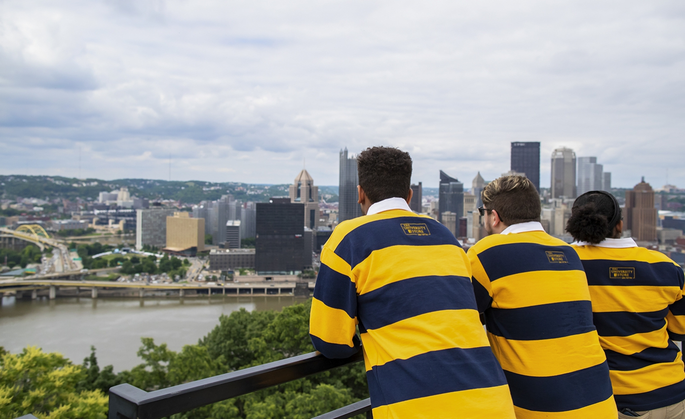 Three Pitt Pathfinder students wearing blue and gold striped rugby shirts look out over the city of Pittsburgh skyline