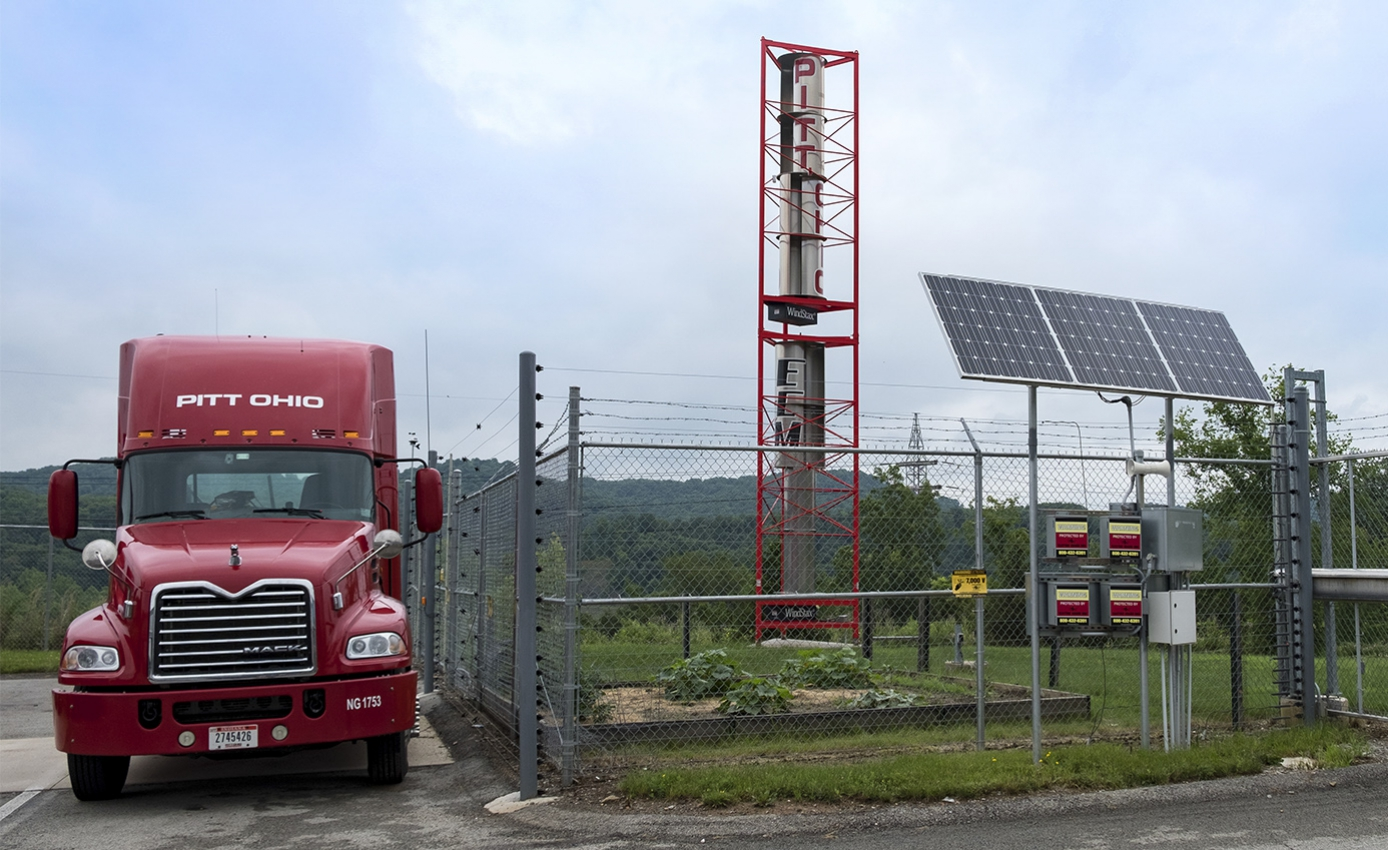 Red tractor trailer parked next to wind turbine and solar panels